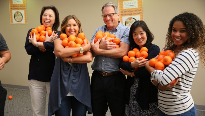 Photo of doctors and staff holding an armful of orange-shaped stress balls during the Best of OC 2017 celebration