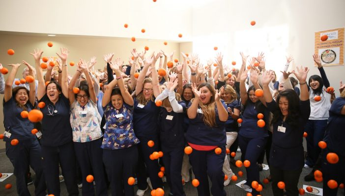 Photo of orange-shaped stress balls being dropped over staff during Best of OC 2017 celebration
