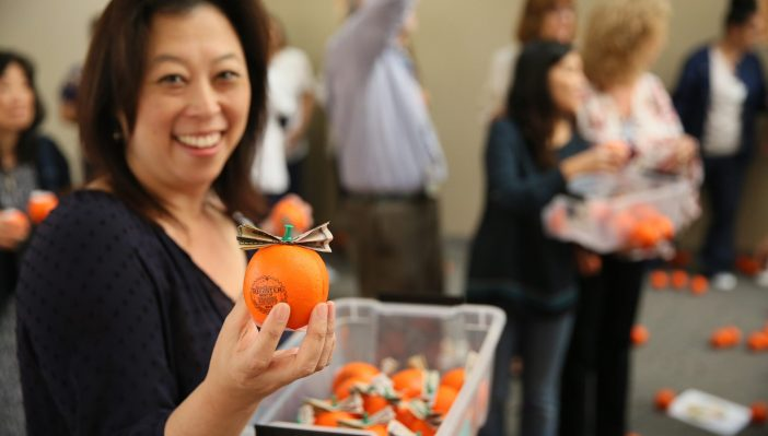 Photo of Dr. Don holding a container filled with orange-shaped stress balls with money pinned to the top to give to staff as appreciation gift for winning Best of OC 2017