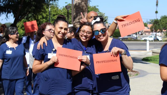 Photo of staff holding up orange, one-word signs that say understanding, professional, and thriving during Best of OC 2018 celebration